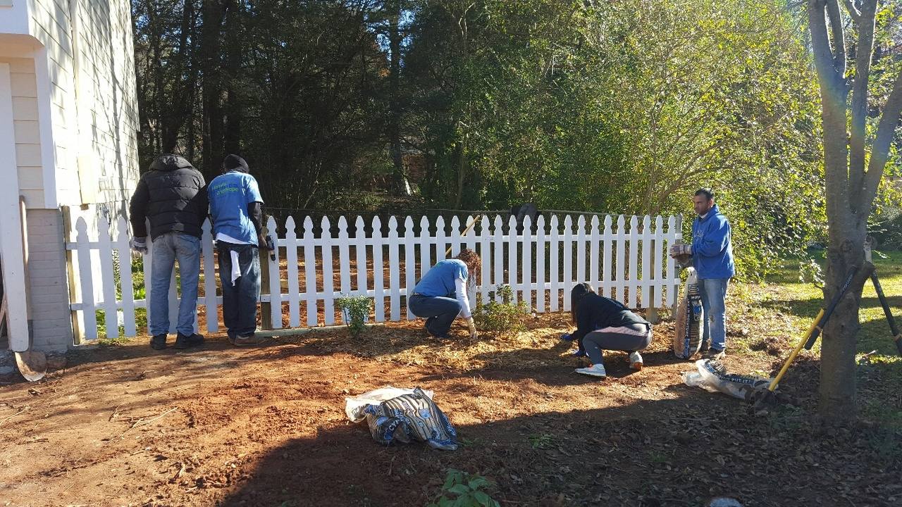 Volunteers plant donated landscaping materials.