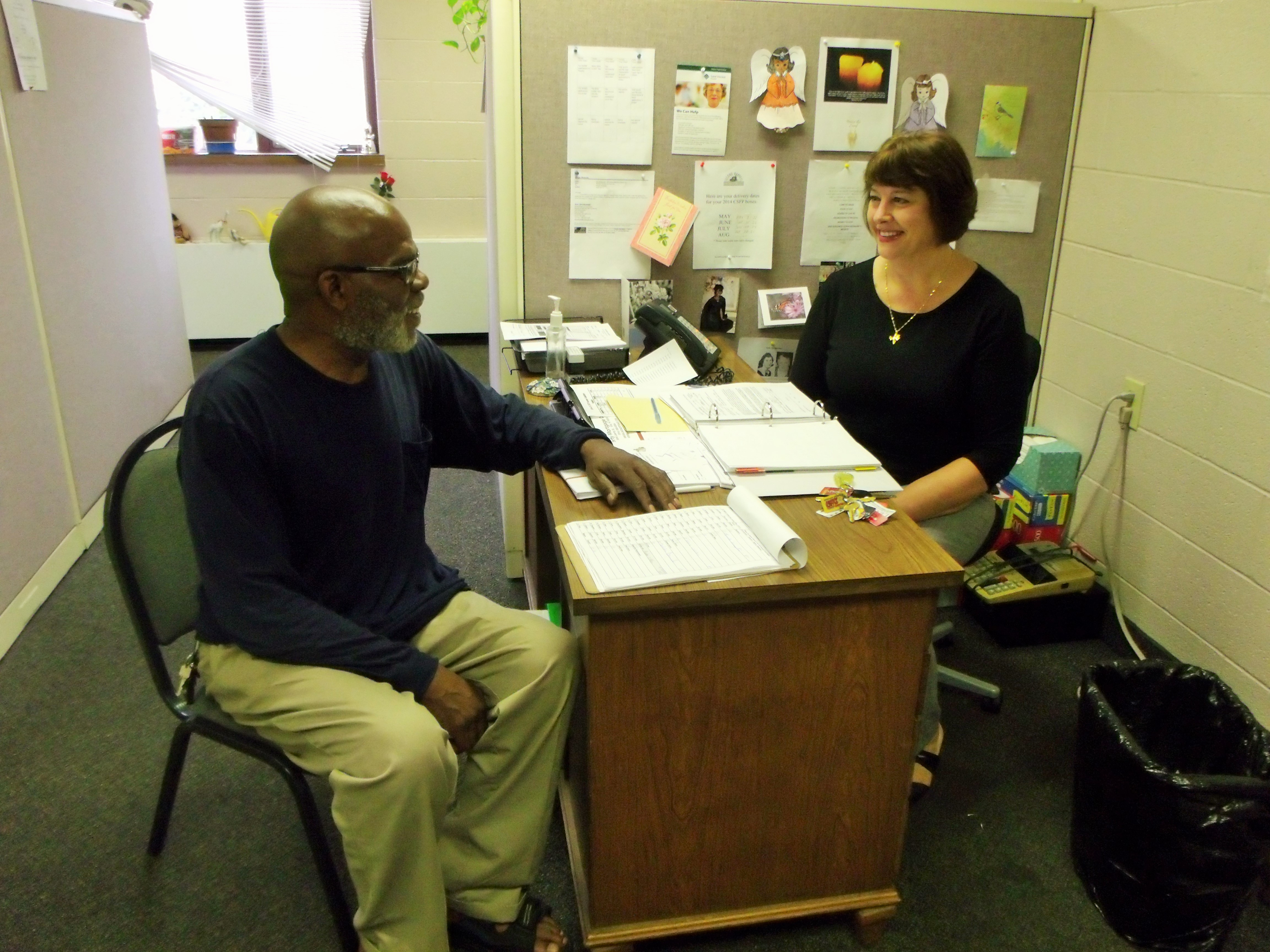 A woman provides counseling to a man as they sit on opposite sides of a desk.