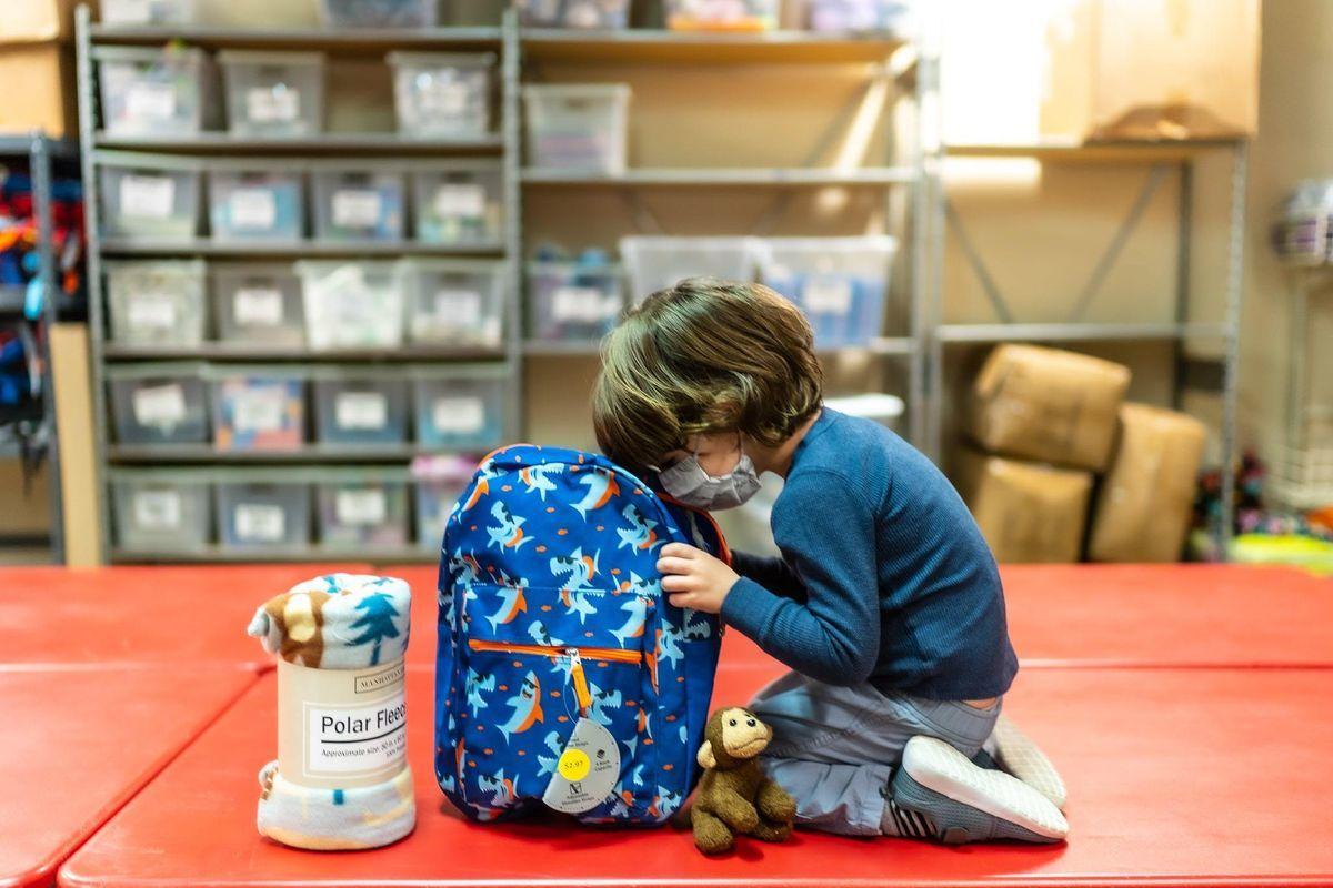 Kid looking inside of backpack.