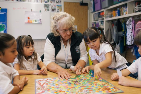 Children and elderly woman playing candy land.