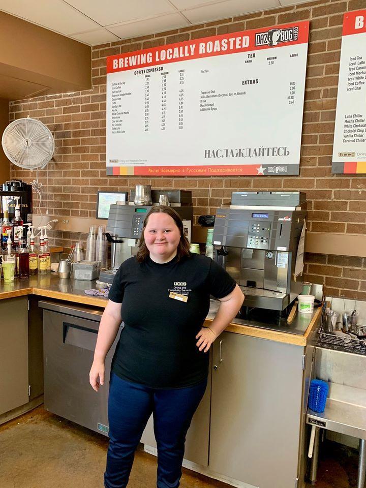 Mia standing in coffee shop wearing uniform