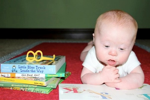 Child with Down syndrome looking through a book.