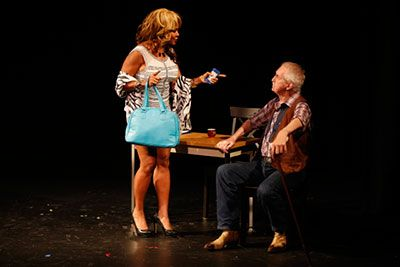 A woman is standing wearing a grey dress, grey shawl holding a turquoise bag in one hand. In another hand, holding a bar of deodorant and pointing to the man sitting at a table listening to her. The man is wearing a plaid shirt, jeans and holding a cane.