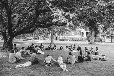 A group of Friends sitting in a circle under the shade of a large tree on the lawn of Hood College in 2016.