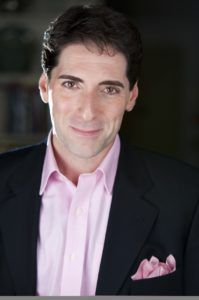 Nicholas Viselli, Artistic Director. A man who is wearing a suit with a pink shirt and posing for the picture.
