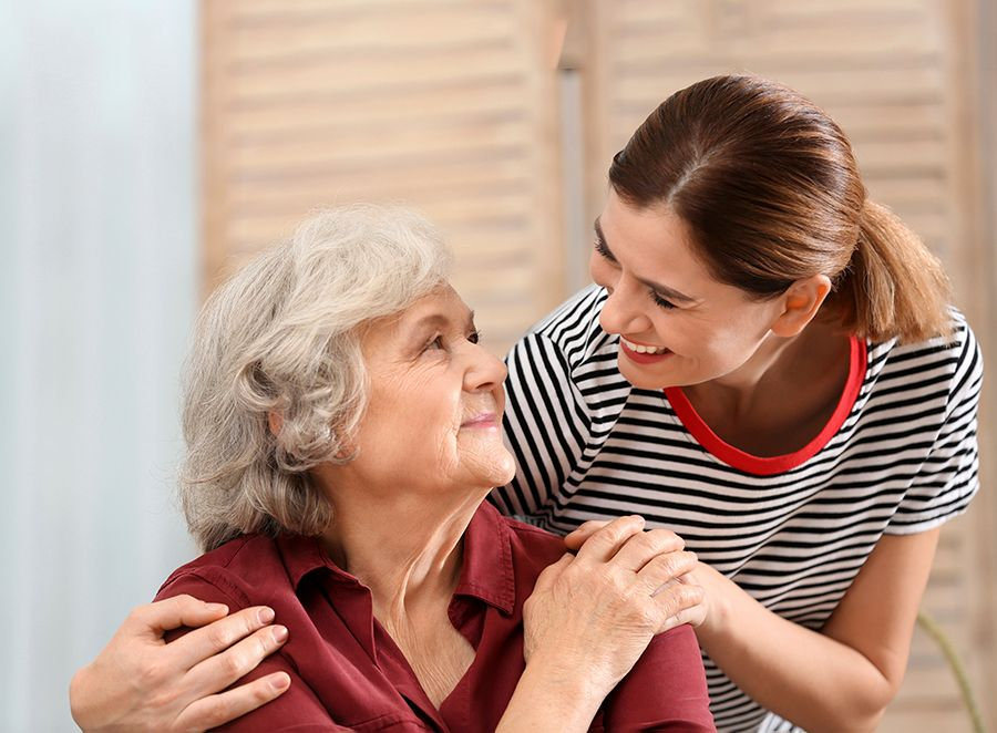 Older woman sitting at home, looking up at a younger woman who has her arm on her shoulder