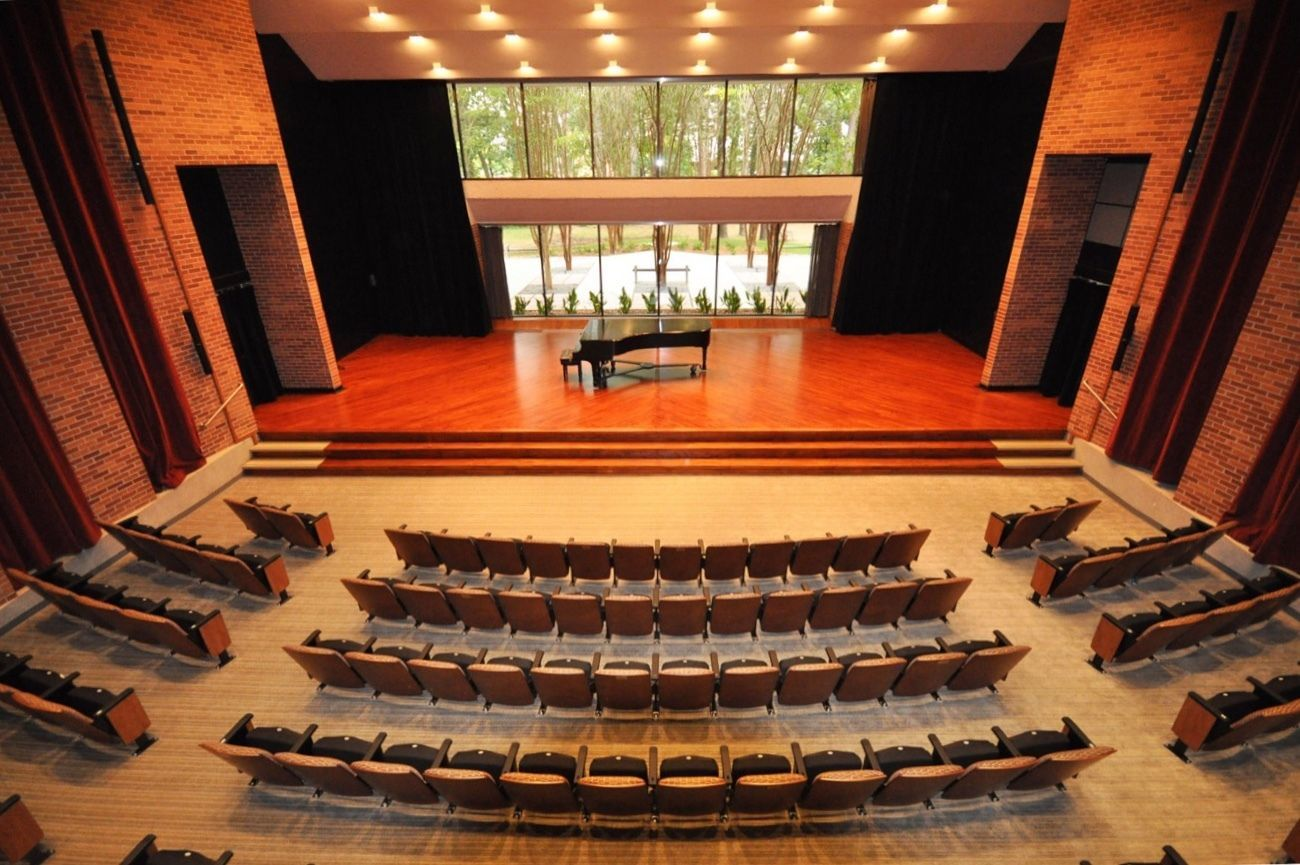 The empty Stella Boyle Smith Concert Hall at UA Little Rock. A grand Piano sits on a stage with large glass windows behind it overlooking the garden outside the building.