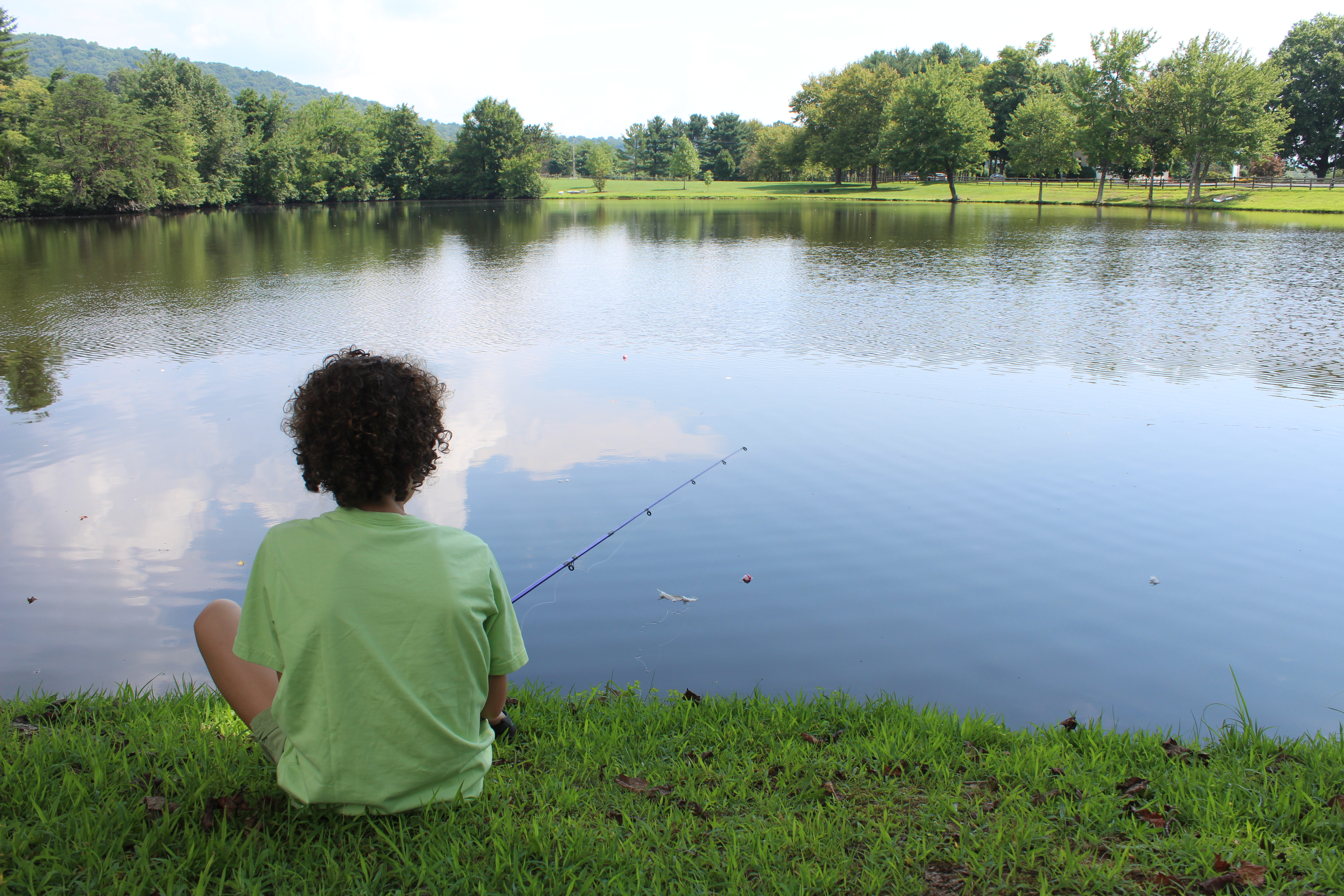 A camper fishes by the lake.