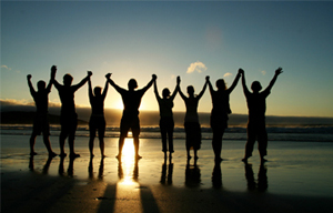 Eight people raise their arms above their heads while holding hands.  They are standing on a sandy beach with their feet touching the water and the sun is setting in the distance.