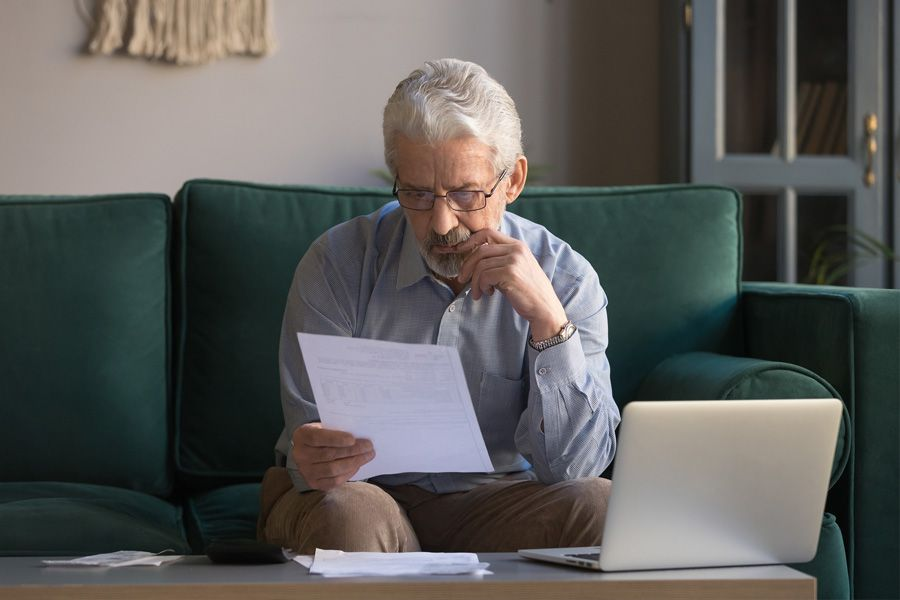 Older man sitting on his couch in front of his laptop, holding and focusing on an important paper