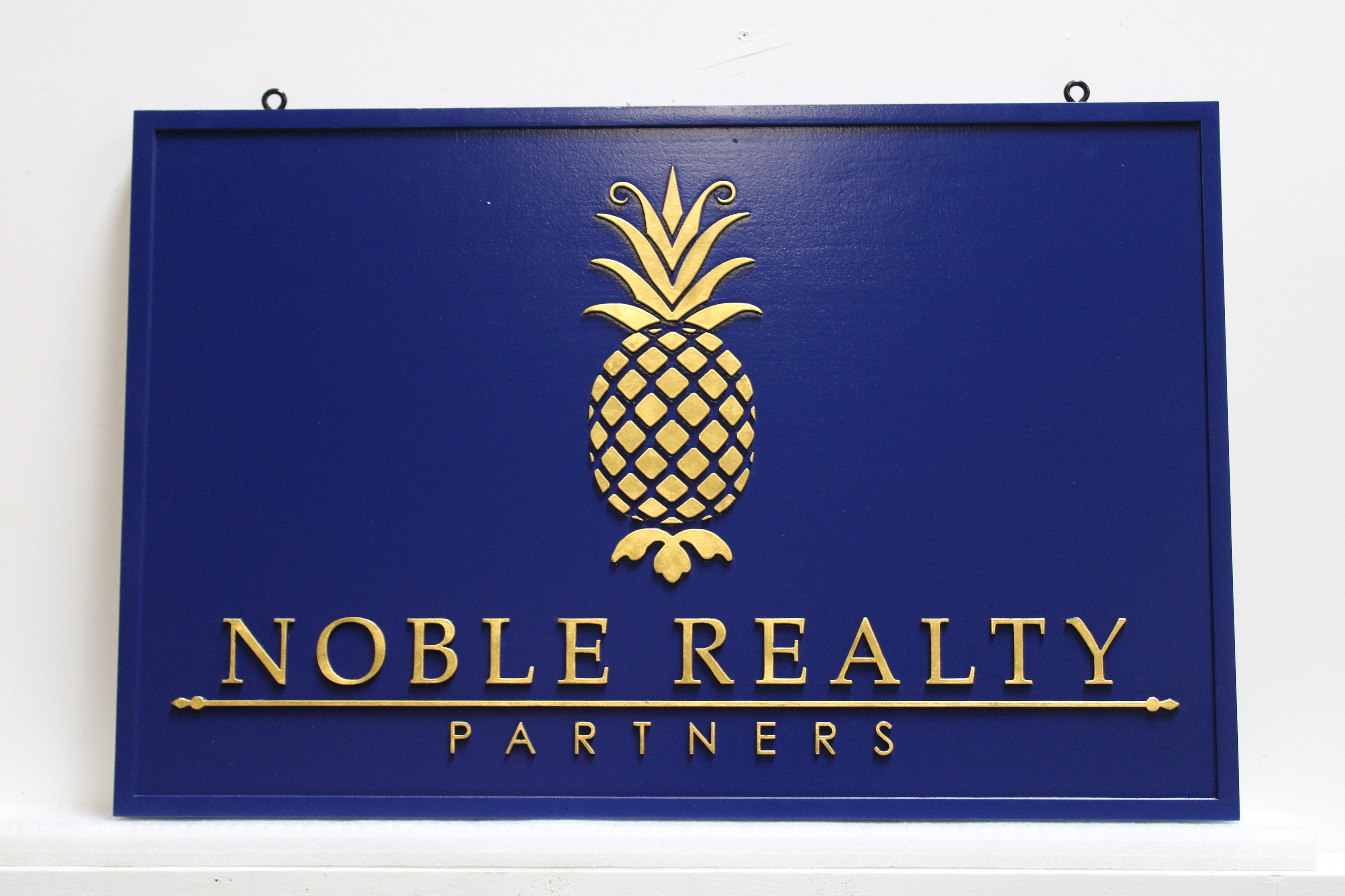 C12288 - Carved 24K Gold-Leaf Gilded  Raised Text and Pineapple  Sign for the Noble Realty Partners