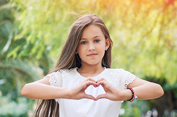Girl making a heart symbol with hands