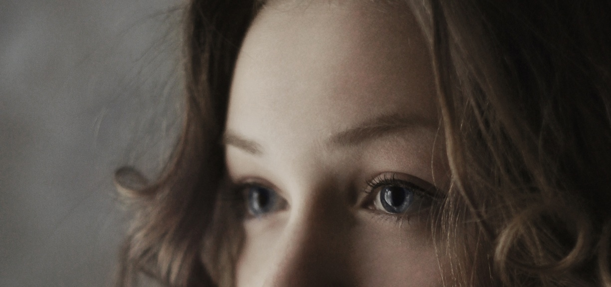 Close up of a young woman with big blue eyes.