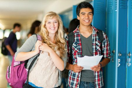 Two high school students standing side by side. On the left is female, and on the right is a male. The female is holding a backpack and the male is holding papers.