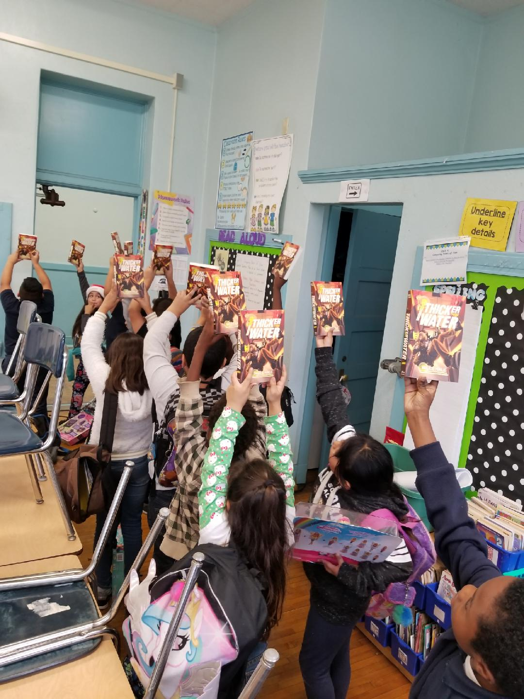 Kids with books in the air.