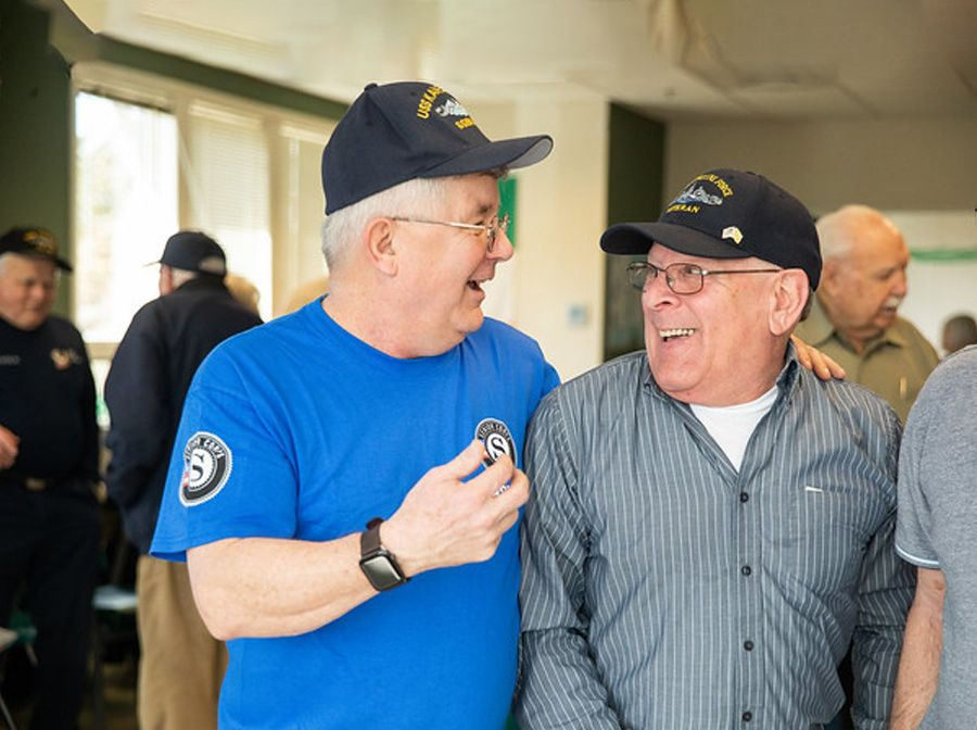 Two older men, one is wearing a Senior Corps t-shirt with his hand over the other man's shoulder. The friends are smiling and talking.
