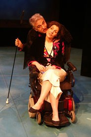 George is hunched over, holding a long black stick and wearing a black outfit. Ann is sitting in her power wheelchair and wearing a black sweater and a red blouse with a white skirt. She's tilting her head to the side. They're posing.