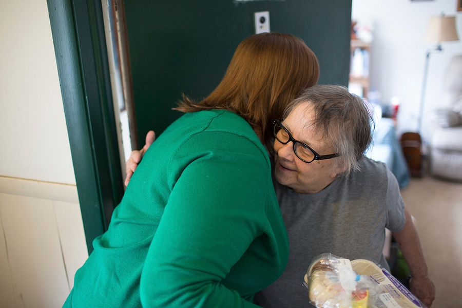 Older woman smiling and hugging volunteer who delivered her meal