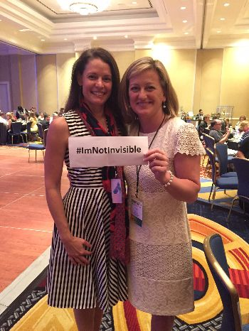 Photo of Dr. Jennifer Lentz and Carol Brill holding a sign that reads #ImNotInvisible