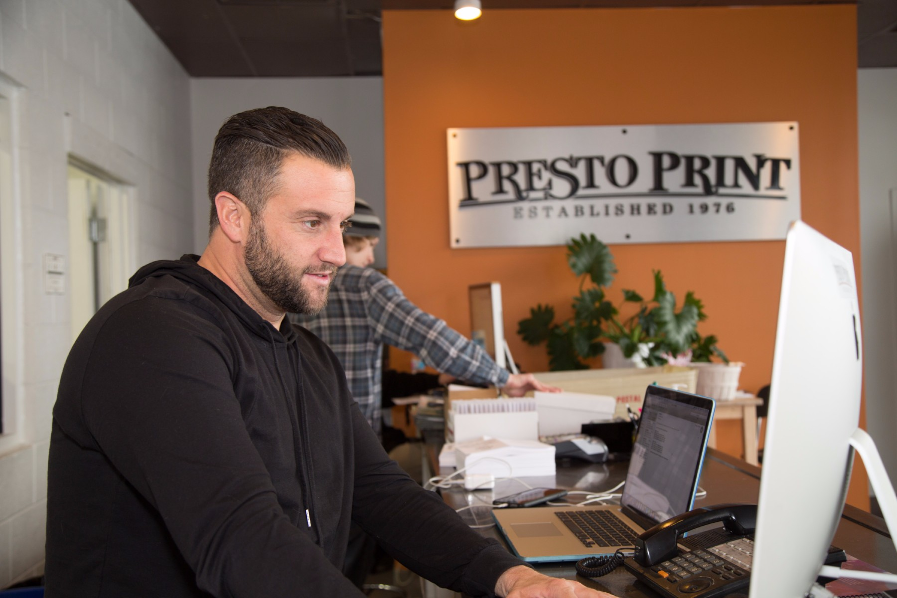 Presto Print employee offering printing services