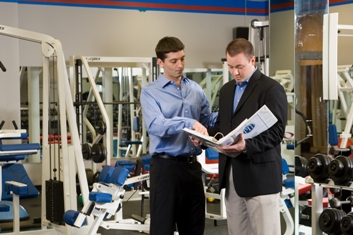 A photo of a PTP New Canaan trainer showing a new client information on training regimens and gym equipment
