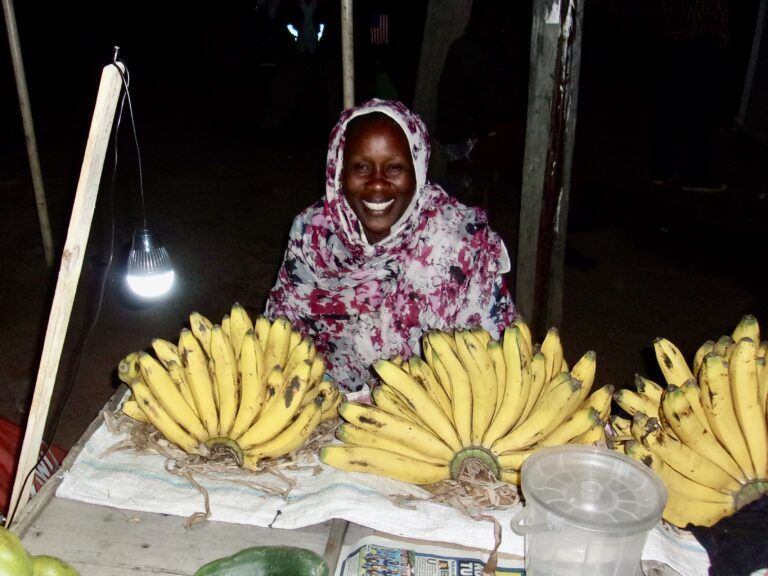 Woman sitting by a table with bananas.
