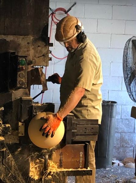 He's making wooden bowls from tree trunks
