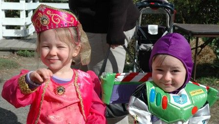 A picture of two young children dressed up in Halloween costumes. One is dressed up as Jasmine from Aladdin and one is Buzz Lightyear from Toy Story