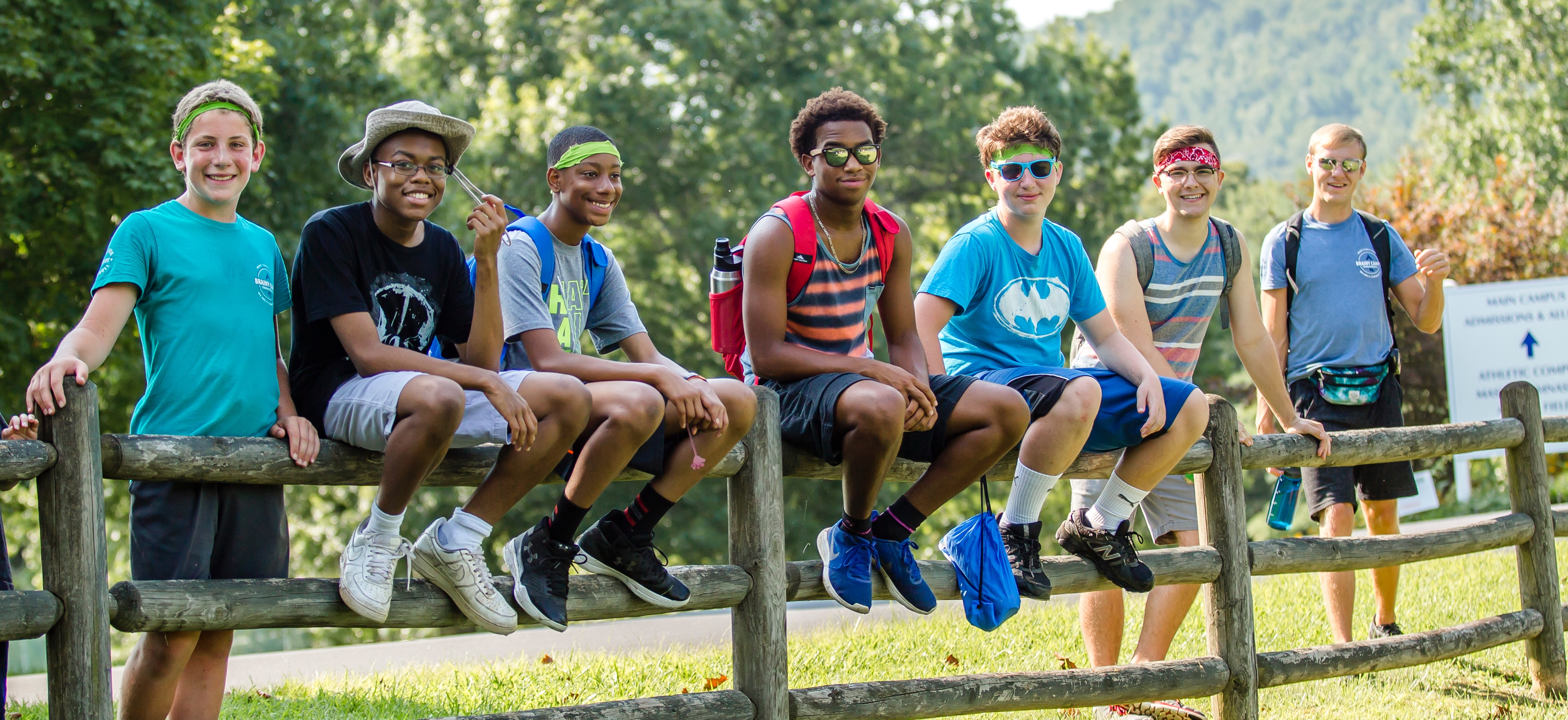 Campers and counselors sit and stand by fence.