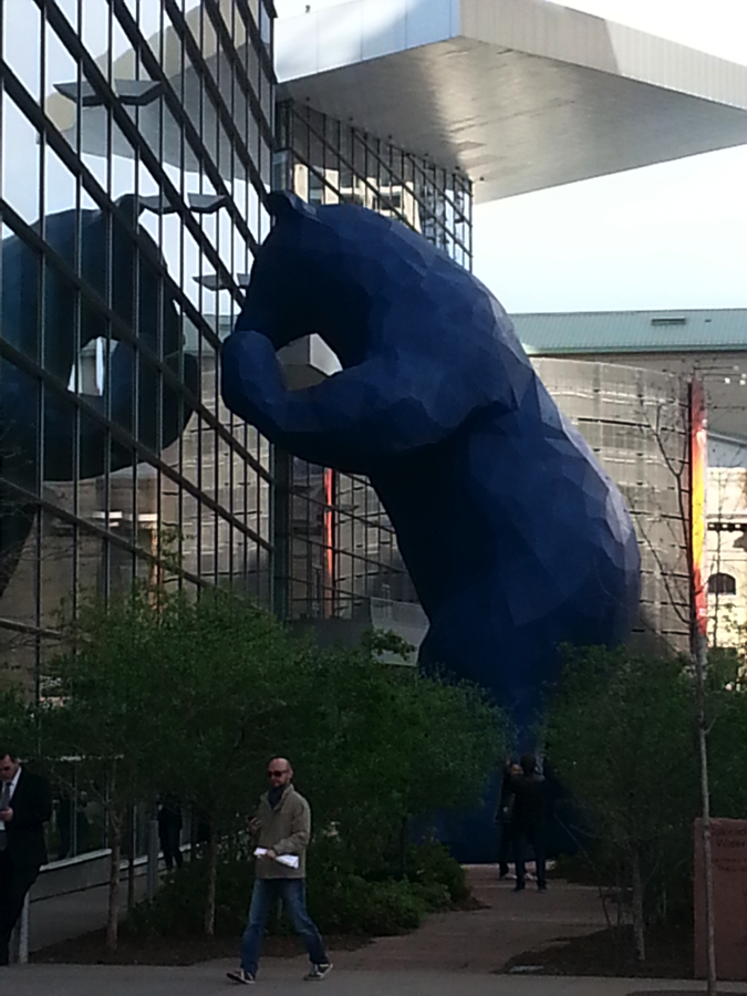 A picture of a 40-foot-tall Blue Bear sculpture peeking into a window