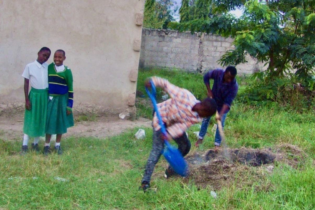 Students digging a hole.