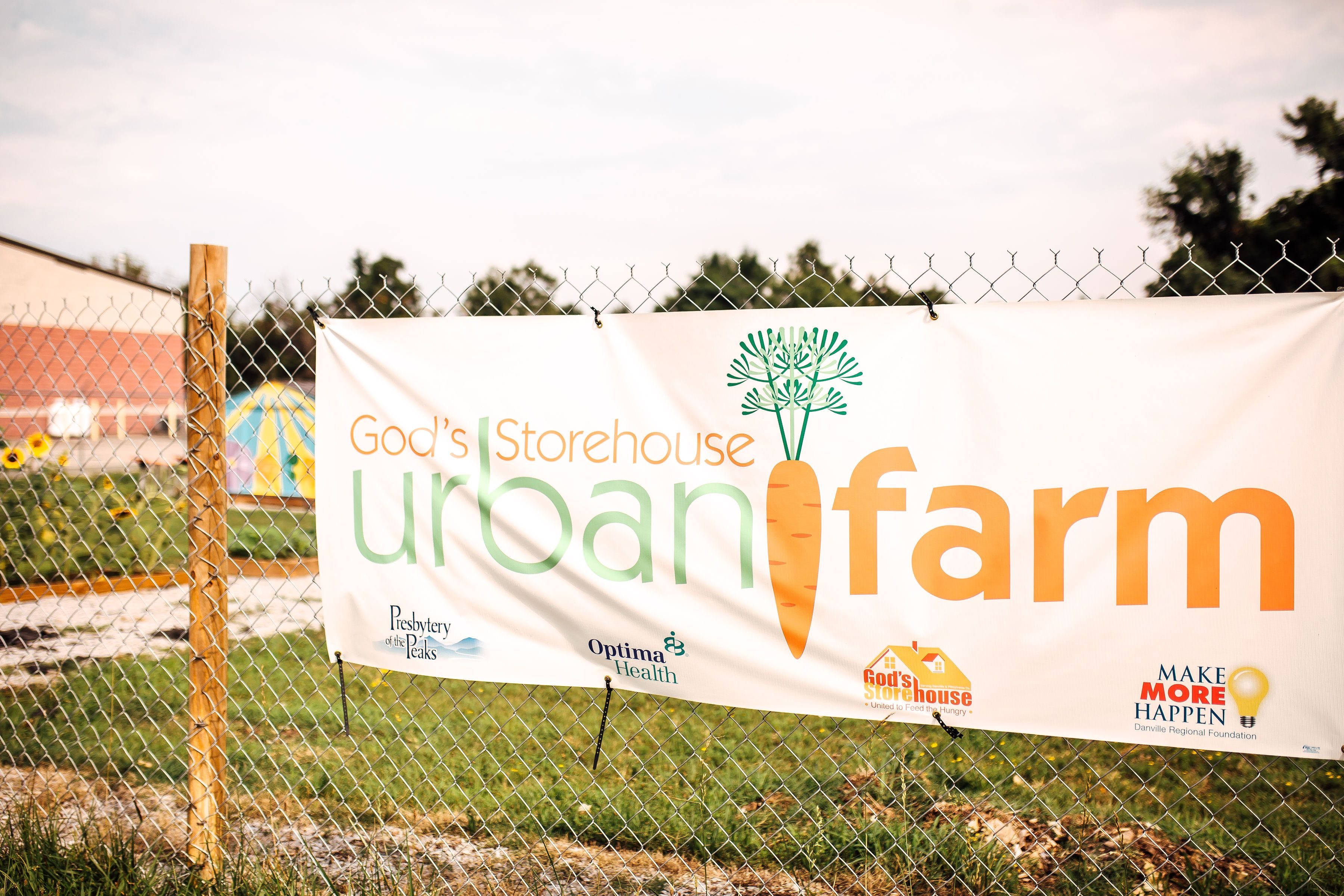 Urban Farm logo on a sign in front of the urban farm lot beside God's Storehouse