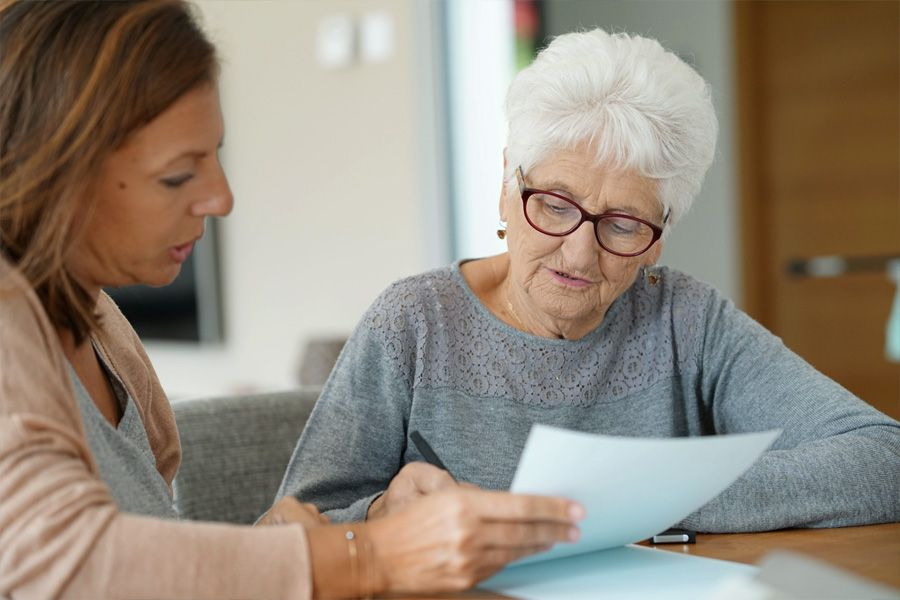 Professional, female, helping older woman will paperwork at kitchen table