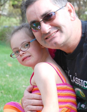 A father holding his daughter with Down syndrome.
