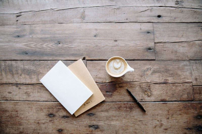 Envelop with company newsletter sitting next to cup of coffee
