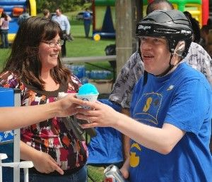 (Left) Woman standing and smiling, looking at person next to her.  (Right)  Man supported by PSRS wearing helmet, reaching out to accept a blue sno cone from somone (only their arm is visible)