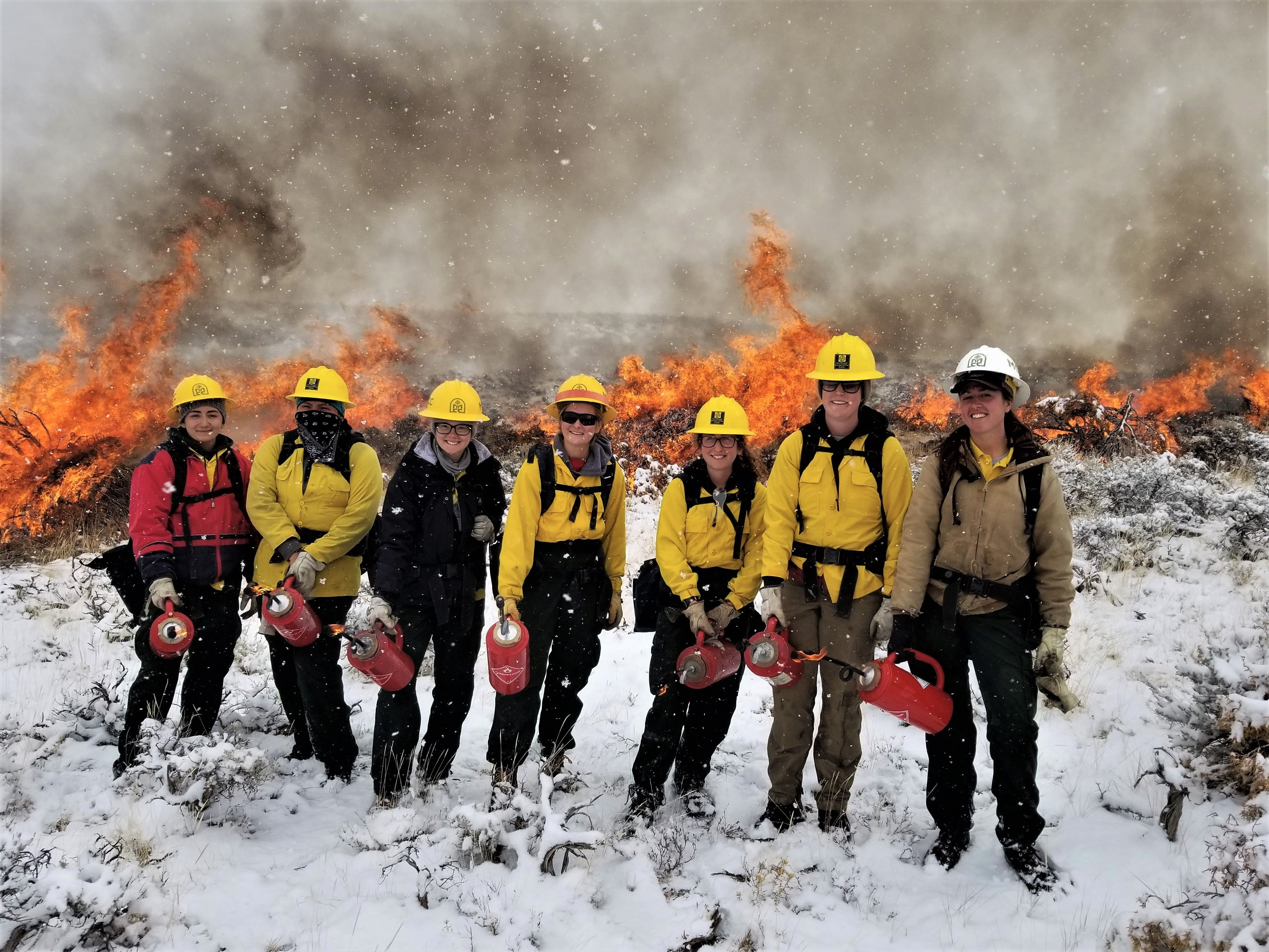 Women standing in protective gear including helmets and chaps. One of the females is wearing the white leader helmet. they are holding fire extinguishing devices and there in snow on the ground but a large fire behind them from burn piles