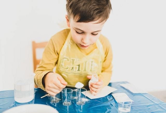 Child in yellow shirt doing science