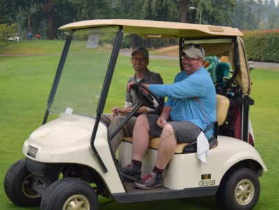 Executive Director Chad drives golf cart with SL Director Paul