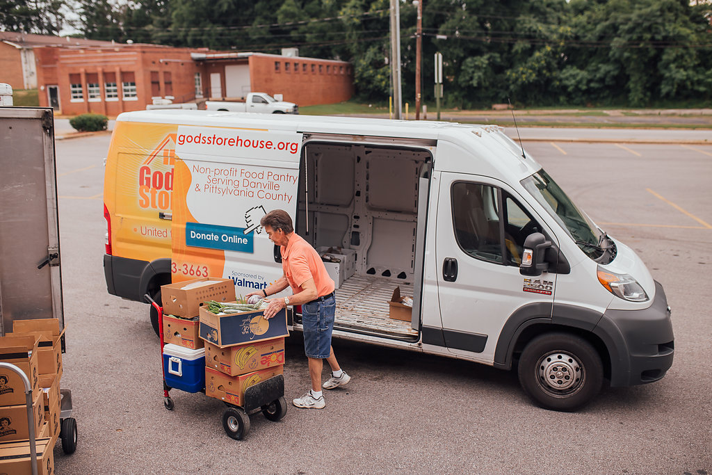 Man loading food boxes from a trolley into a van.