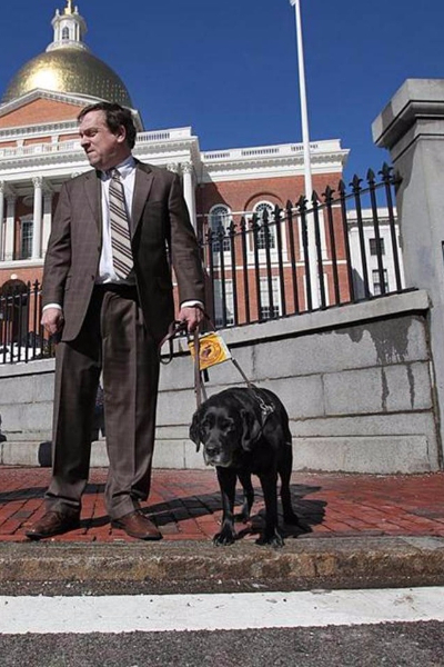 Carl Richardson in front of the Massachusetts State House with guide dog Kinley