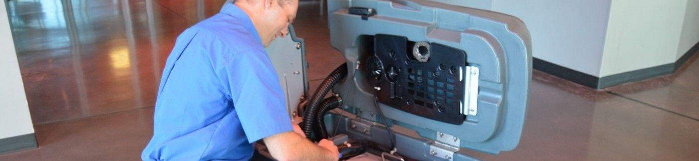 Man Servicing Janitorial Floor Equipment