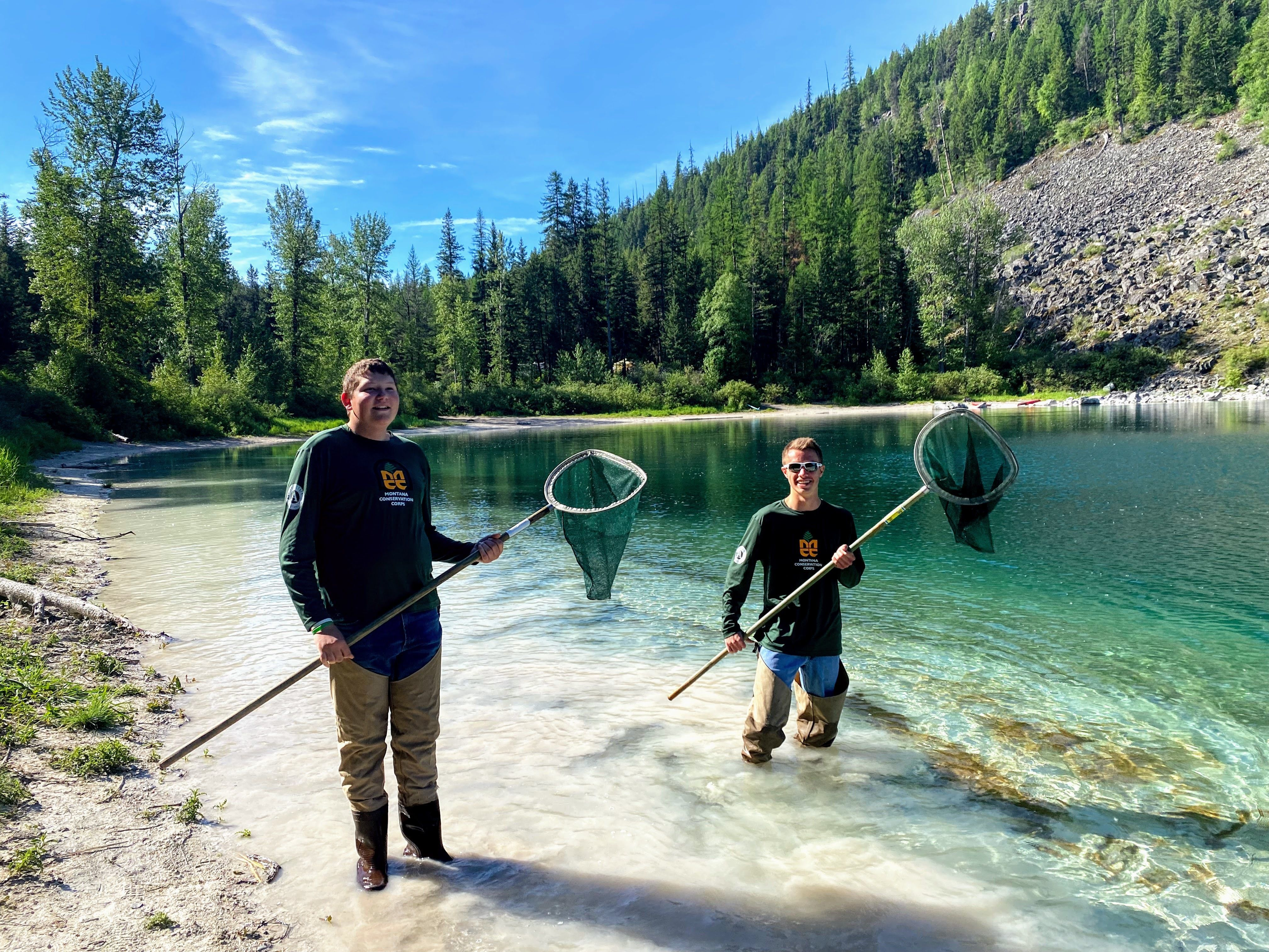 A youth member and a crew leader stand in a pond with nets