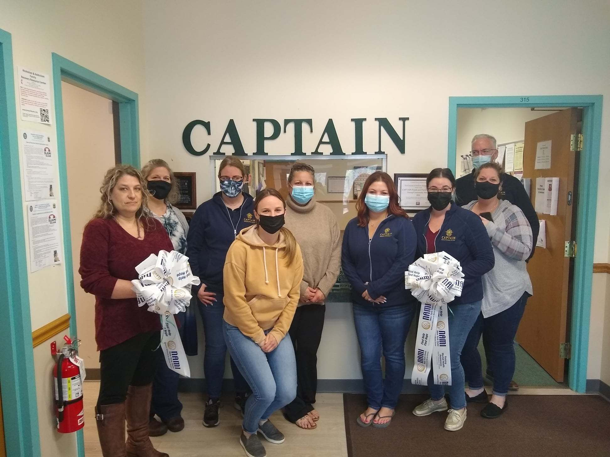 Staff at the Clifton Park office posing with ribbons from NAMI New York State which will be displayed in support of NAMI's mission and having a mentally healthy workplace!