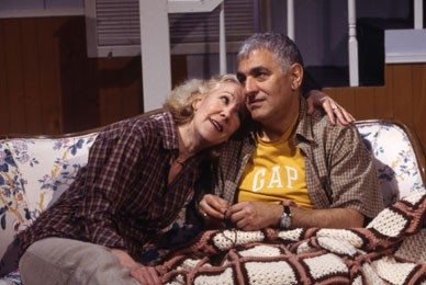 Melanie Boland, and George Ashiotis. A couple are sitting on the couch. They are partially covered by a blanket and the wife is leaning and gazing into her husband's eyes. They are wearing comfortable clothing.