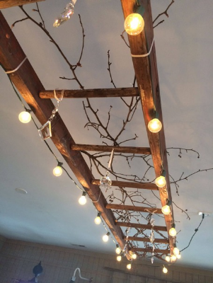 Upcycle and old ladder for a one-of-a-kind lighting fixture.