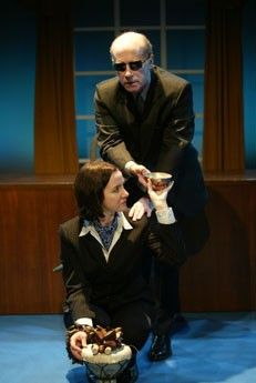 Pamela is wearing a suit, a blue scarf and kneeling holding a tray with her head turned listening to J. Martin. He's wearing dark glasses, sitting behind Pamela on the edge of a window. He's wearing a suit, trying to grab the tray.