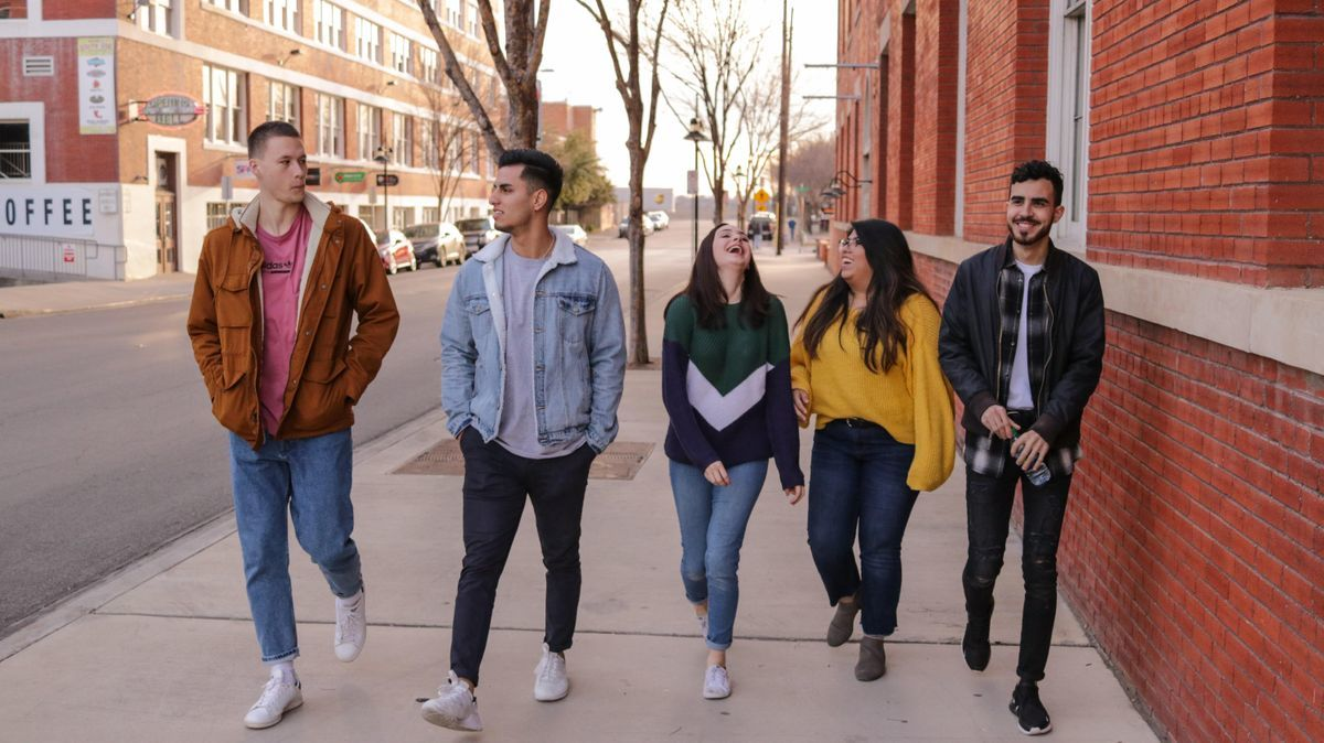 Five students walk down sidewalk downtown