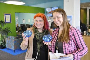 Volunteers holding blue piggy banks