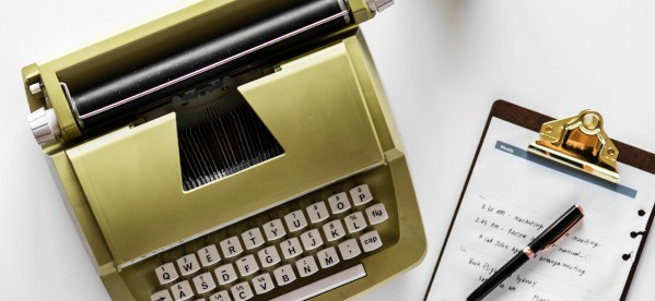 Typewriter and clipboard side by side